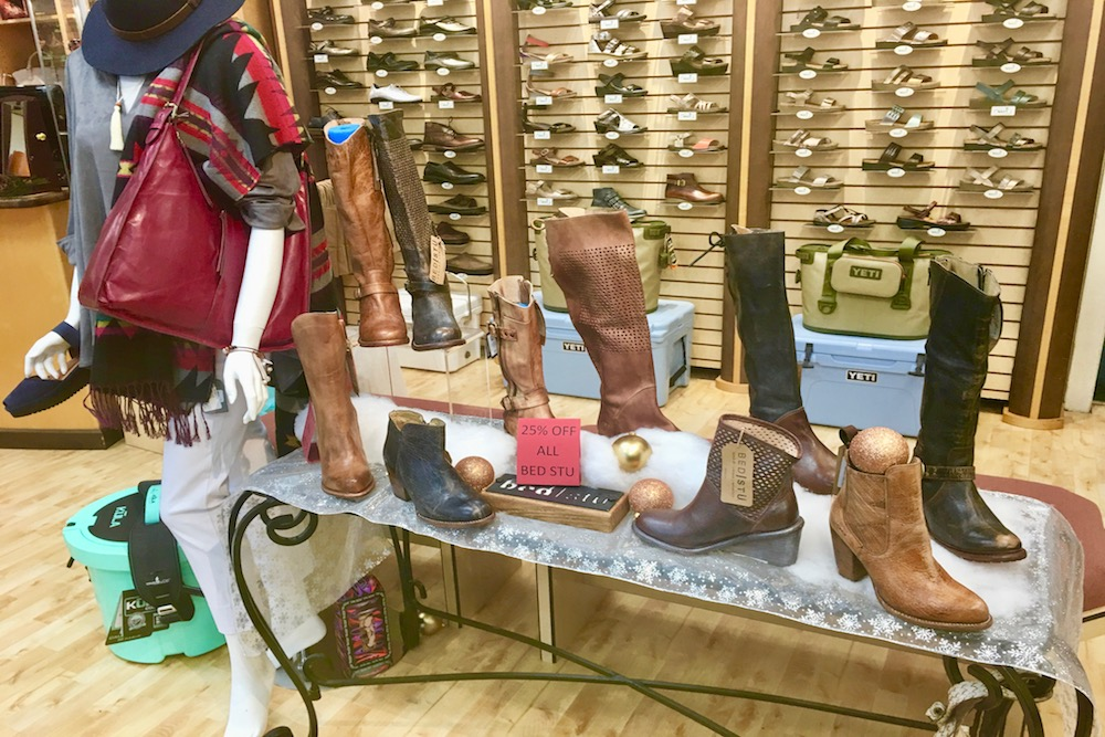 An iron table with an assortment of women's leather boots on display at Sunset Shoes in Sandestin, Florida.