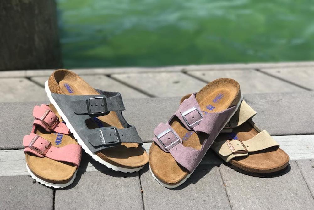 4 individual Birkenstock sandals in purple, tan, pink, and grey sitting on a wooden dock.