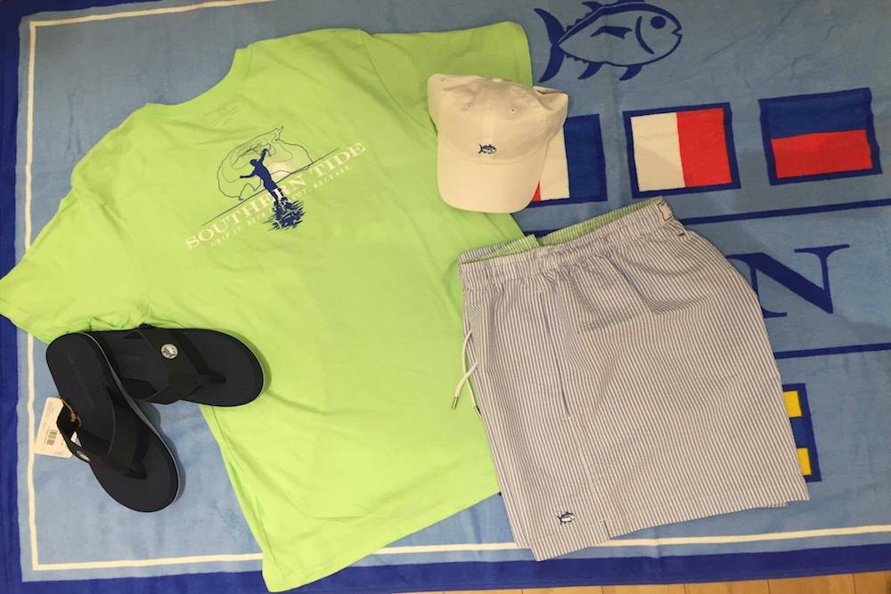 A green Souther Tide t-shirt, blue and white striped swim trunks, black flip flops, and a white Southern Tide hat sitting on top of a blue towel at Sunset Shoes.
