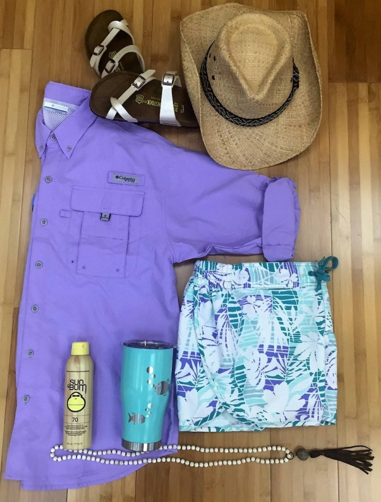 A purple Columbia button up shirt, white Birkenstocks, a straw sunhat, floral print swim trunks, a can of Sun Bum sunscreen, a turquoise metal cup and a beaded necklace.