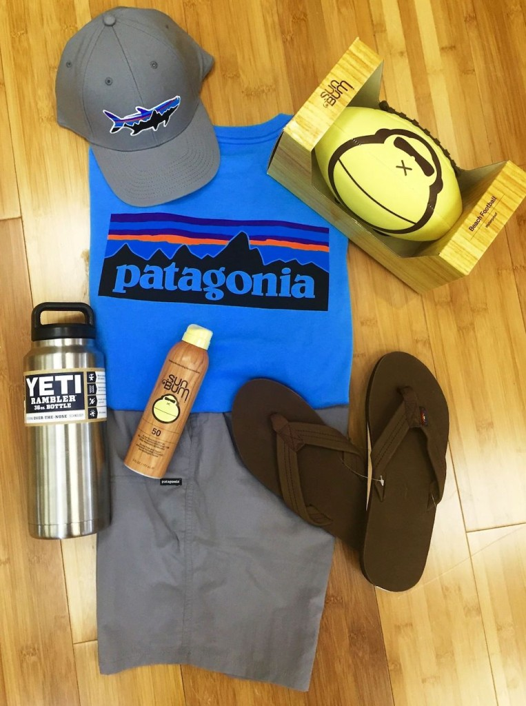 A grey hat, blue t-shirt, and grey shorts from Patagonia with a Yeti Rambler, Sun Bum sunscreen, and black flip flops at Sunset Shoes.
