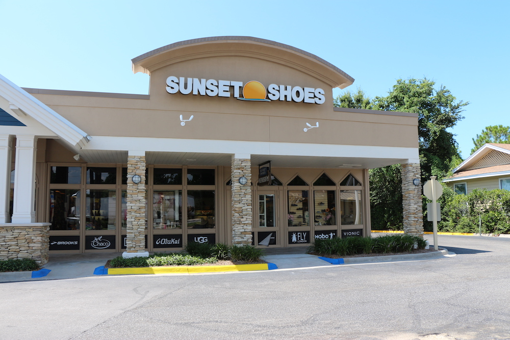The storefront of Sunset Shoes with a portion of the parking lot in view.
