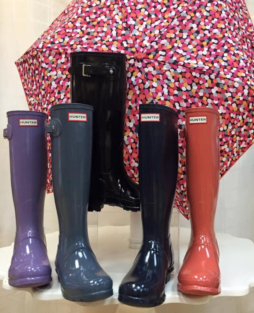 A display of 4 individual Hunter rubber boots in black, blue, grey, purple, and orange in front of a multi-colored umbrella at Sunset Shoes in Sandestin, Florida.