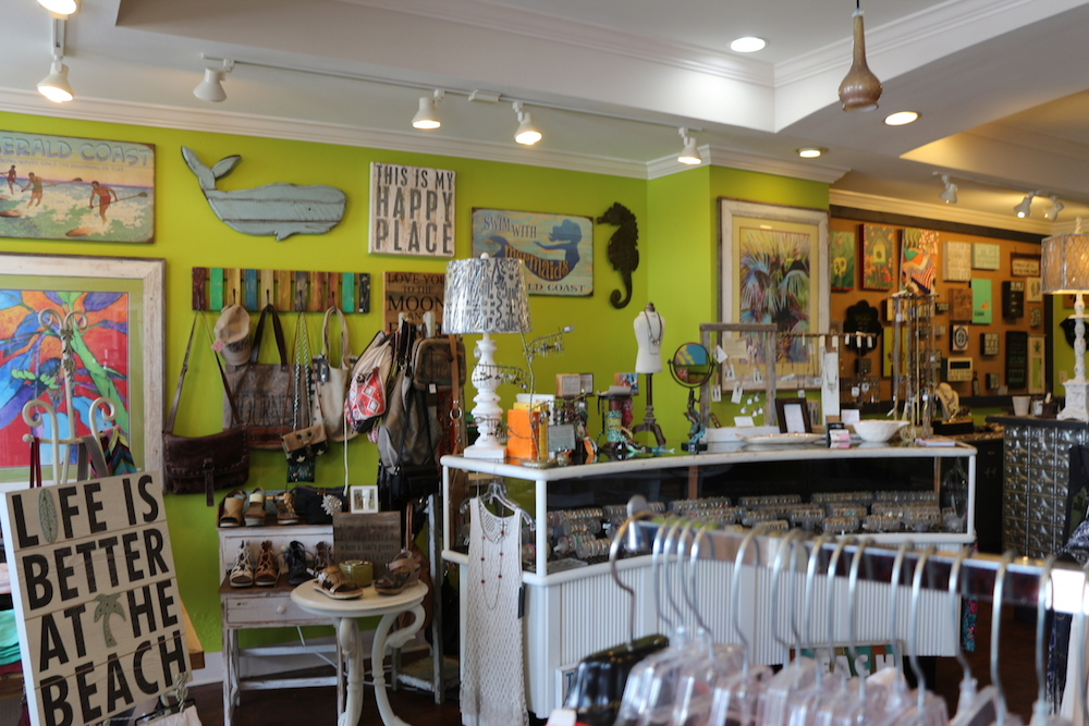 A green wall with an assortment of wooden signs hanging on it at Favori Boutique in Sandestin, Florida.