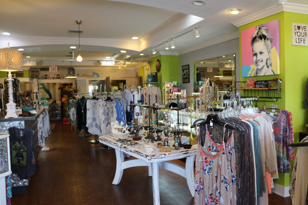Racks of women's shirts and a wooden display table with necklaces inside of Favori Boutique in Sandestin, Florida.
