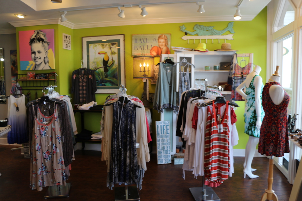 3 individual clothing racks with women's tanktops and shirts inside of Favori Boutique in Sandestin, Florida.