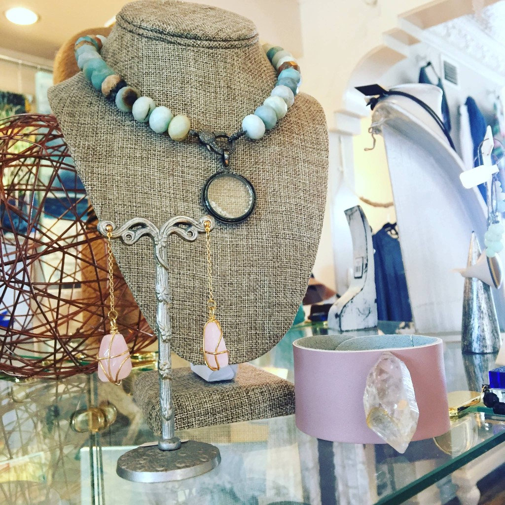 A burlap necklace display with a stone necklace on it in front of a pair of pink stone earrings at Village Boutique.