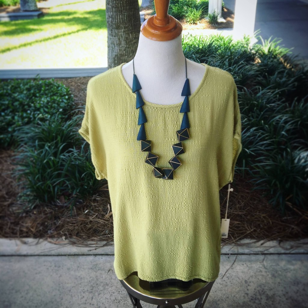 A mannequin wearing a yellow blouse and a blue and gold necklace in front of Village Boutique.