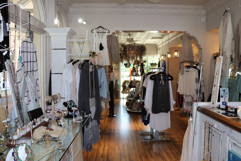 A glass-topped table next to 3 racks of women's clothing at Village Boutique.
