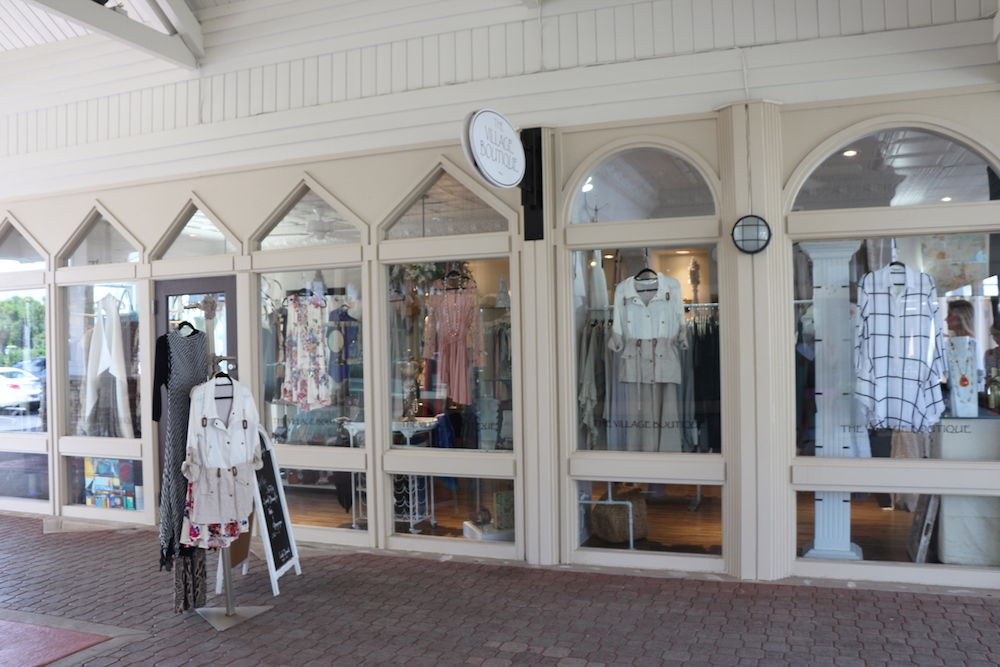 The storefront of the Village Boutique with windows that have clothing displayed behind them.