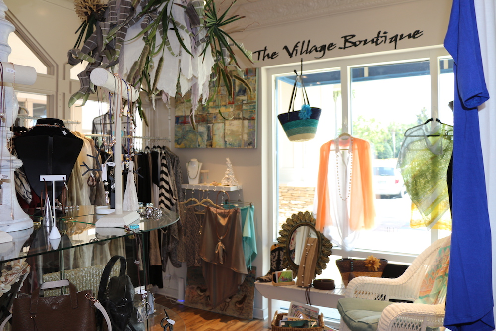 An inside view of the Village boutique with women's clothing and jewelry on display.