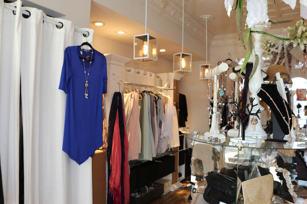 A blue women's blouse hanging outside of a dressing room next to a jewelry display at Village Boutique.