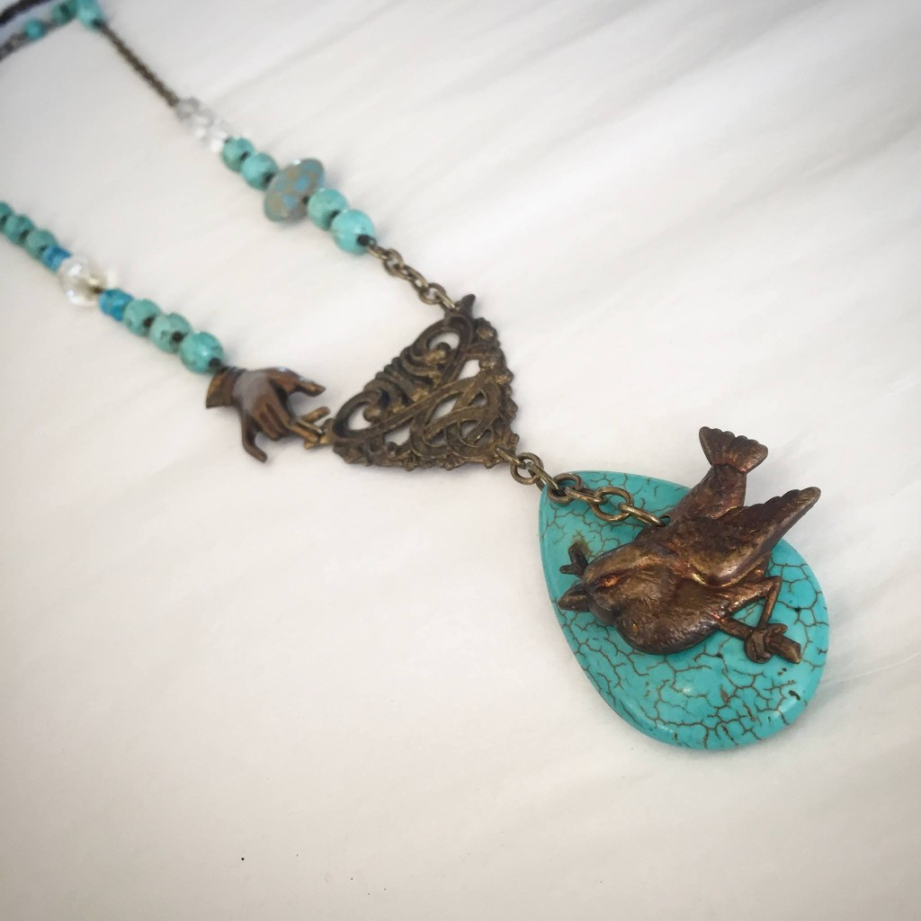 A turqoise beaded necklace with a bronze bird medallion at Village Boutique.