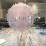 A sticker with the logo of Primp Salon in Sandestin, Florida, stuck on one of the salon's windows.