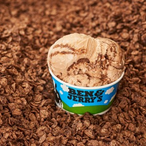 A cup of Ben and Jerry's ice cream sitting on a bed of chocolate cereal.