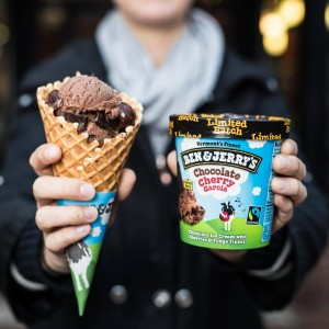A woman holding a waffle cone with chocolate ice cream next to a pint of Chocolate Cherry Garcia ice cream from Ben and Jerry's.