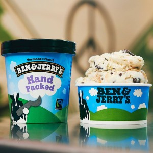 A pint of hand-packed Ben and Jerry's ice cream sitting next to a small cup of ice cream.