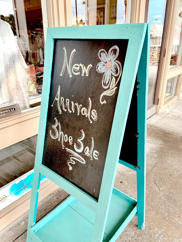 "A turqoise wooden sign with a chalkboard sitting outside of Favori Boutique in Sandestin, Florida with the words ""New Arrivals Shoe Sale"" written on it."