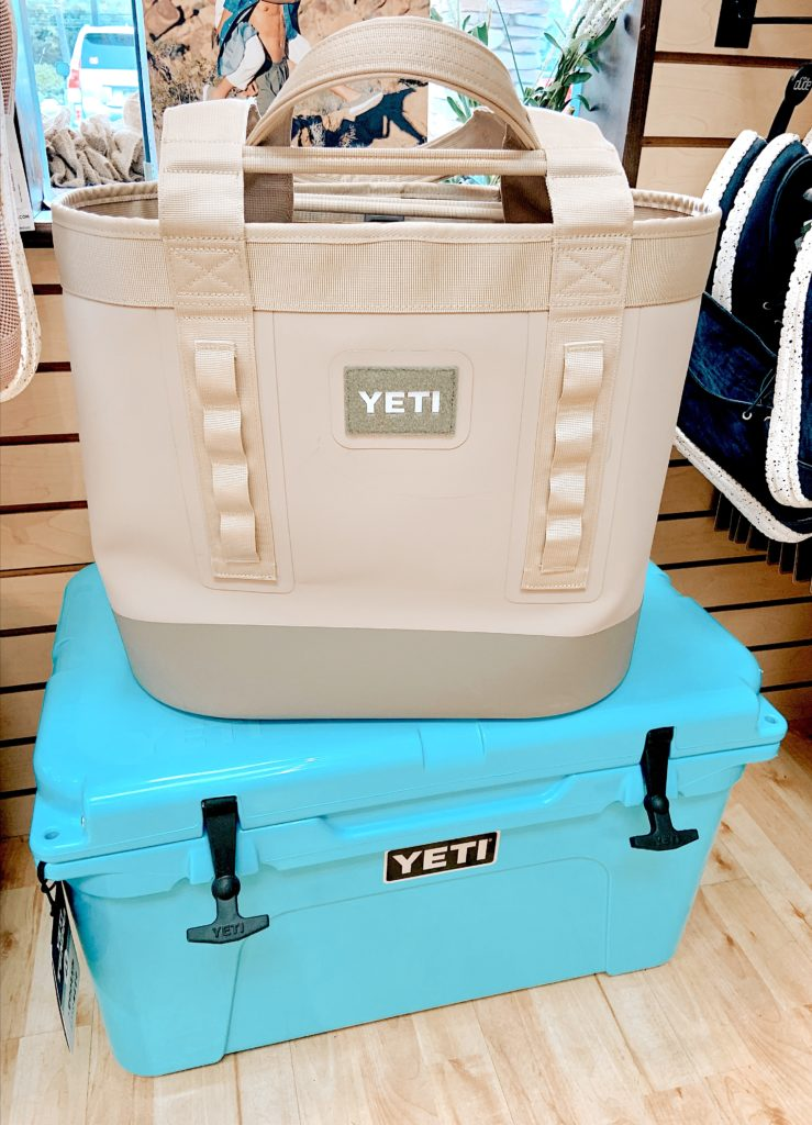 A large, tan cloth Yeti Cooler sitting on top of a turquoise plastic Yeti Cooler at Sunset Shoes in Sandestin, Florida.